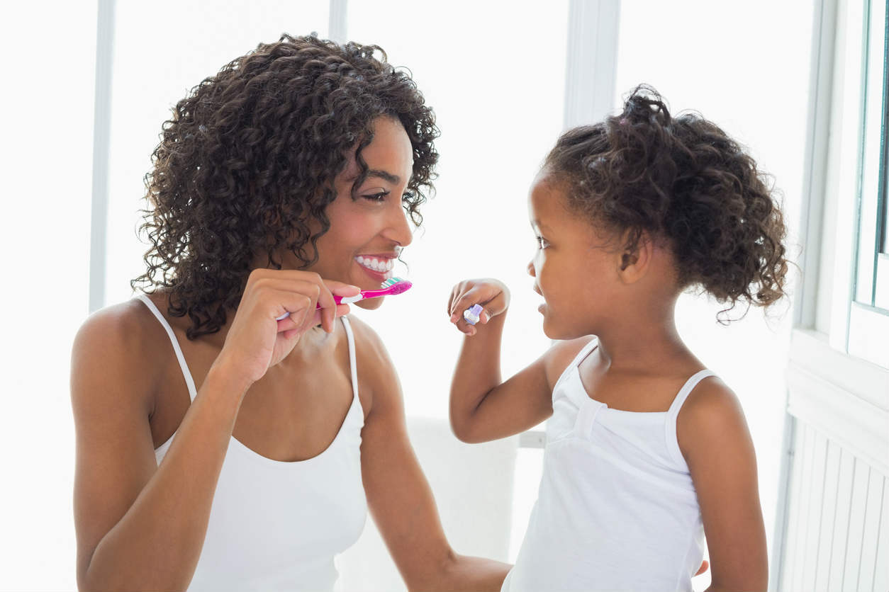 mother teaching daughter to brush teeth