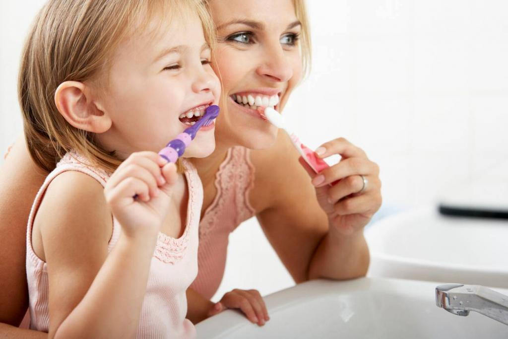 mother helping daughter brush her teeth